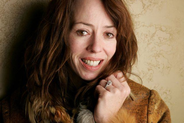 Mackenzie Phillips holds her jacket while posing for a photo.