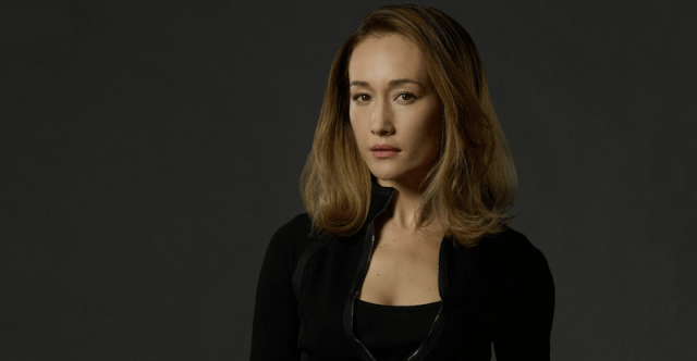 Maggie Q wears black clothes and stands in front of a gray background.