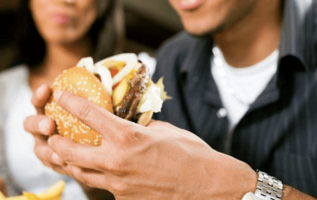A man holds a burger with both hands.