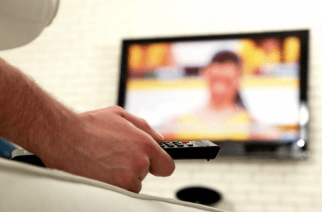 Man with TV remote in hand