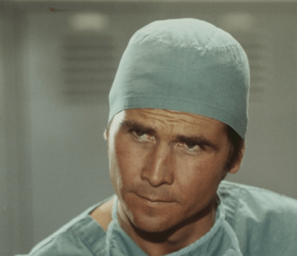 Marcus Welby looking serious in a medical cap and gown.