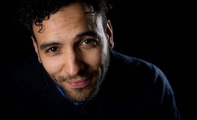 Marwan Kenzari staring straight at the camera and wearing a blue sweater.