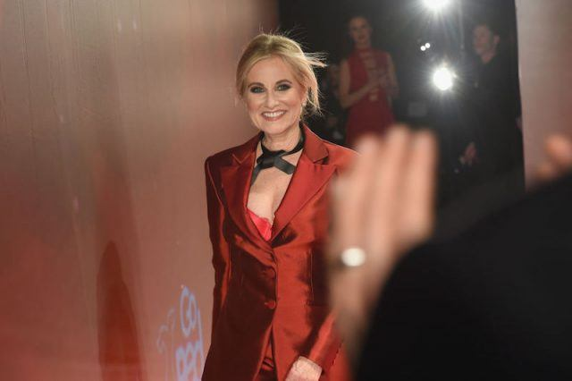 Maureen McCormick walks through a Macy's event wearing a red suit.