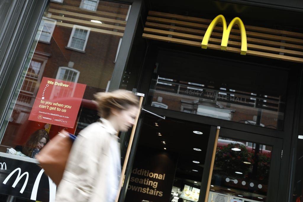 Woman walks past a McDonald's