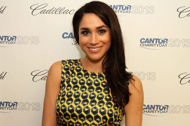 Meghan Markle smiles brightly in a yellow and black dress at a red carpet.