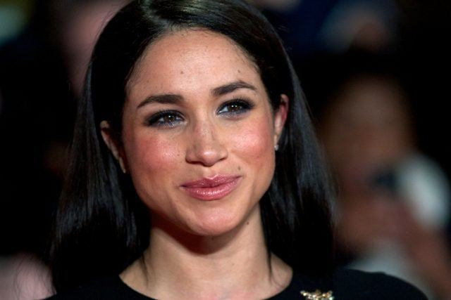 Meghan Markle smiles while attending a movie premiere.
