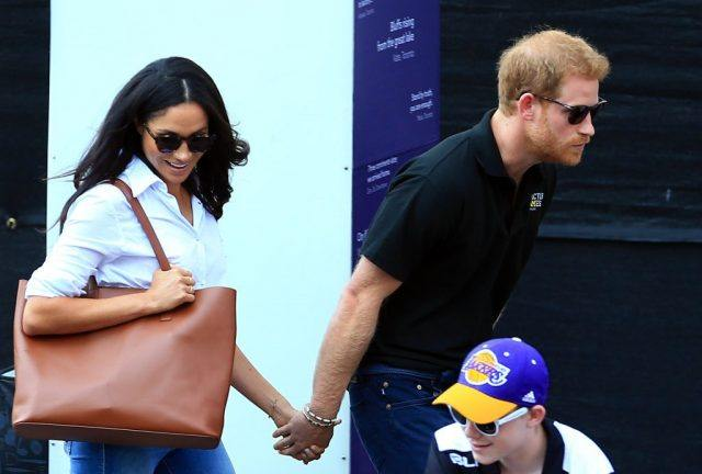 Prince Harry and Meghan Markle hold hands as they walk towards their seats.