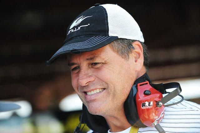 Michael Waltrip smiles while wearing a baseball cap.