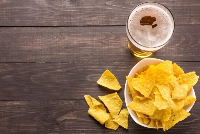 Nacho tortilla chips on a wooden table with beer.