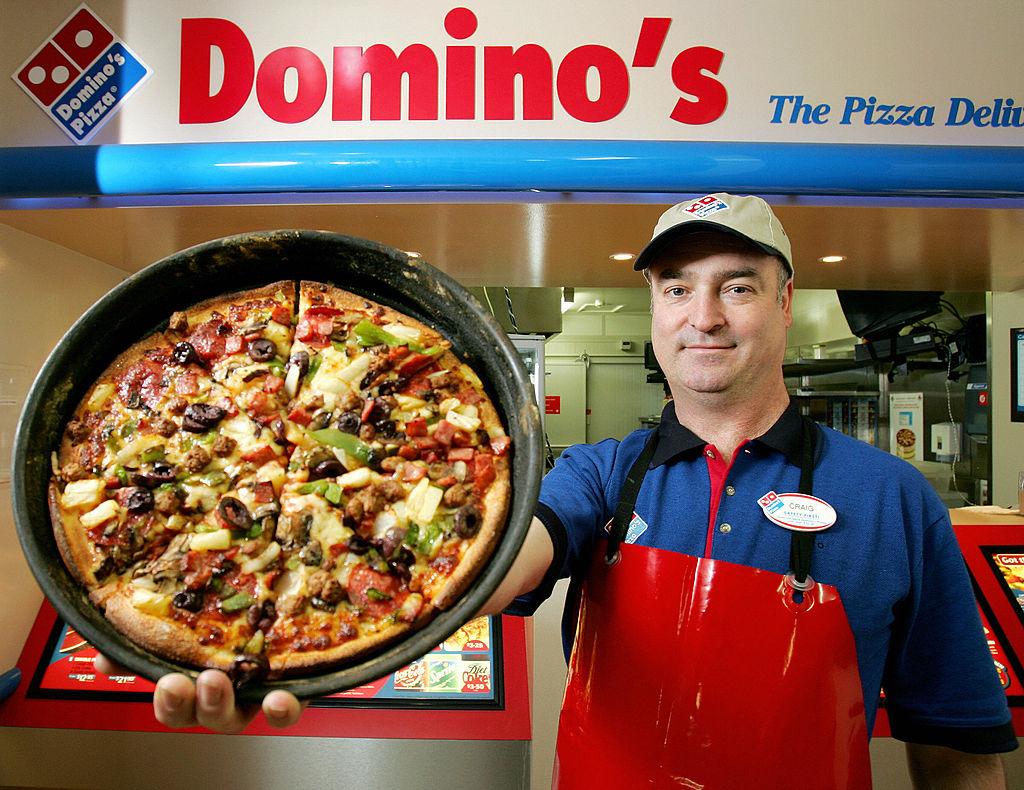 man displays a super supreme pizza