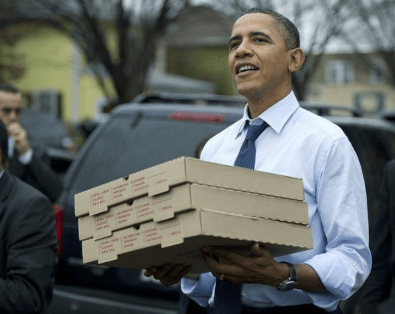 Barack Obama carrying pizza boxes