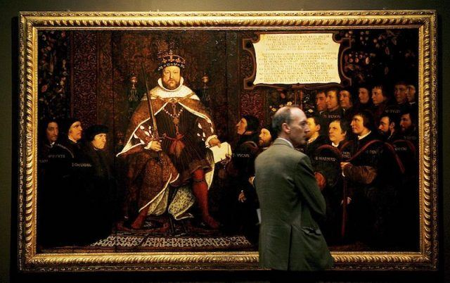 A man in a suit standing in front of a large painting of Henry VIII.