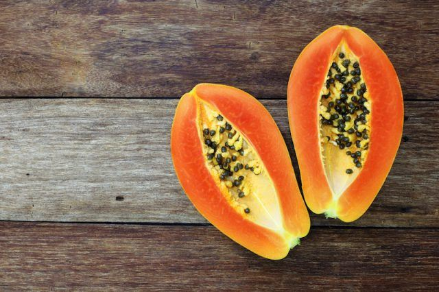 A papaya cut in half on a wooden table.