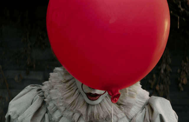 Pennywise stands behind a big red balloon.