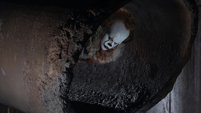 Pennywise sticks his head out of a sewer pipe