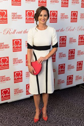 Pippa Middleton poses in a white and black dress with red accessories.