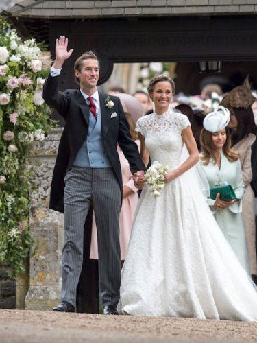 Pippa Middleton holds a bouquet while holding her husband's hand.