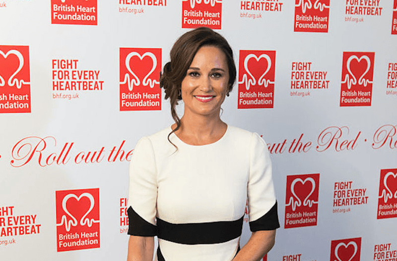 Pippa Middleton stands in a white and black dress