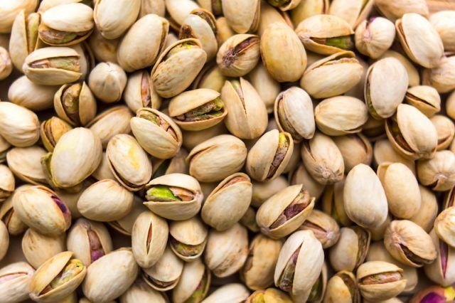 Pistachios in their shells piled together.