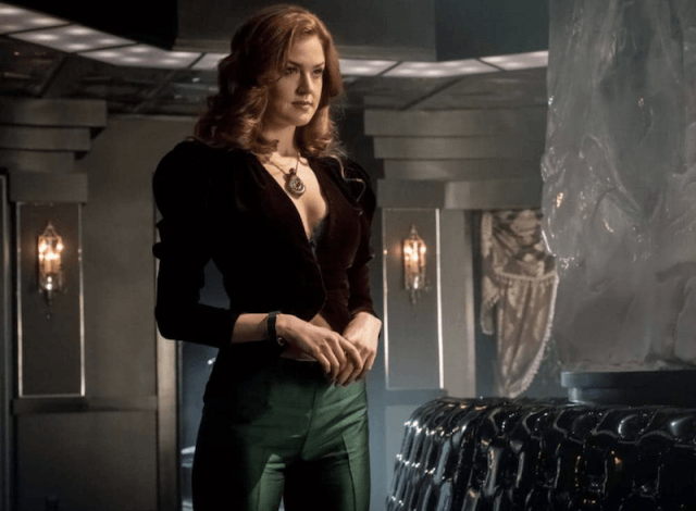 Ivy stands in green pants and a black top