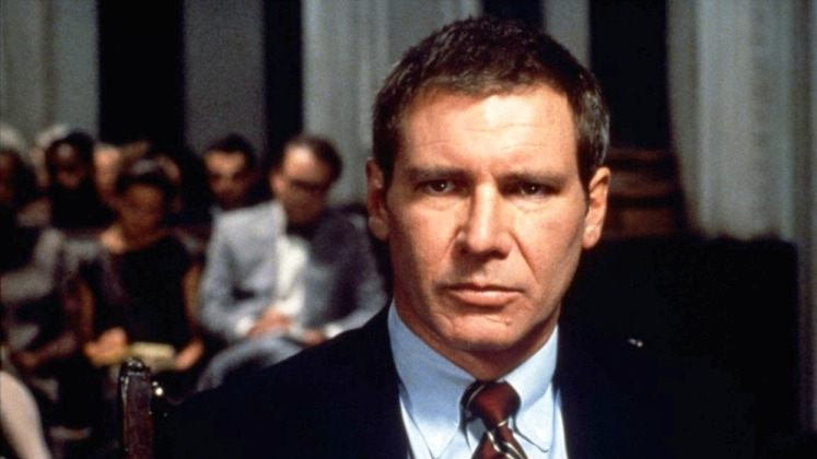 Harrison Ford wears a suit and looks ahead as Rusty Sabich in Presumed Innocent