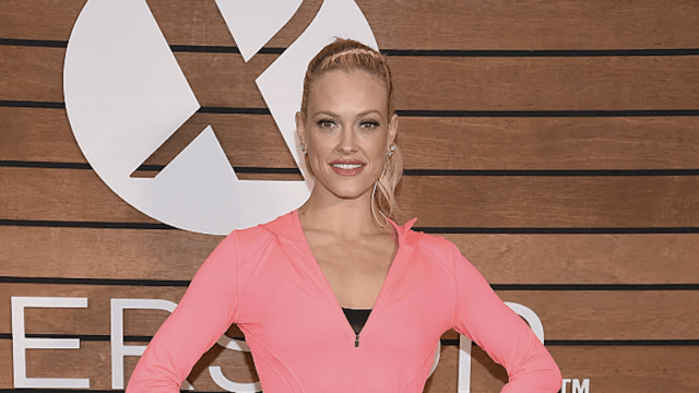 Peta poses in pink fitness gear.