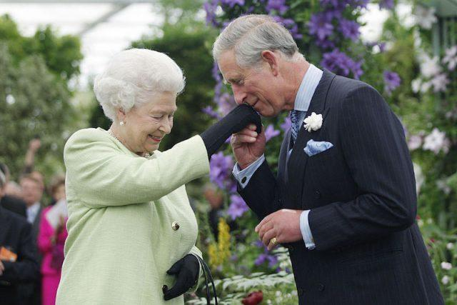 Queen Elizabeth II and Prince Charles outside during a garden party.