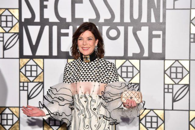 Princess Caroline holding a pink Chanel bag and holding out her palm.
