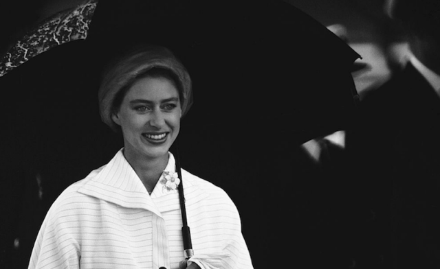Princess Margaret smiling and holding an umbrella.