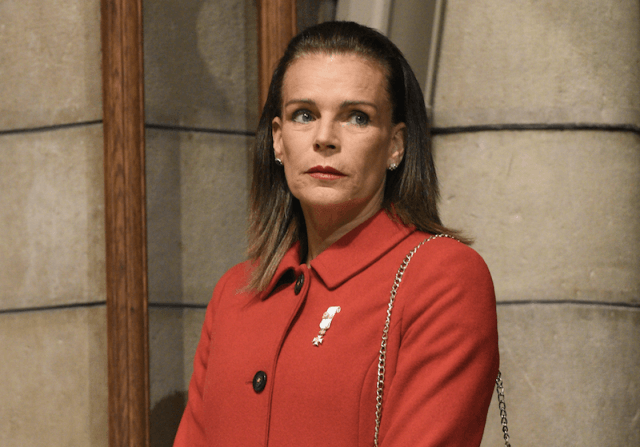 Princess Stephanie of Monaco stands in front of a building wearing an orange coat.