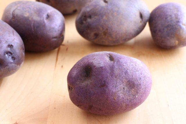 Purple potatoes on wooden table