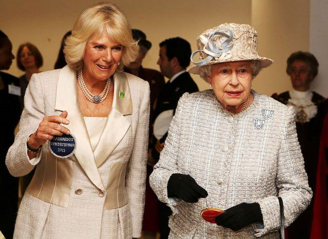 Camilla Parker Bowles and Queen Elizabeth stand together while attending an event.