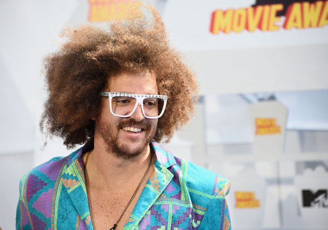 Redfoo smiles while wearing a a colorful suit and white glasses.