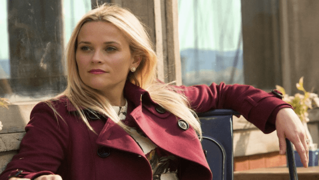 Reese Witherspoon in 'Big Little Lies' wearing a red jacket and sitting outdoors.