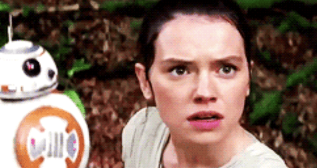 Rey looks upward towards the sky with a confused look on her face.