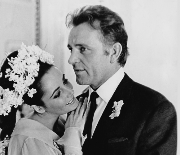 Elizabeth Taylor leans on Richard Burton as she wears flowers on her hair.