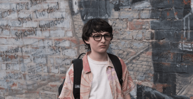 Richie stands wearing his glasses and a backpack in an alley.