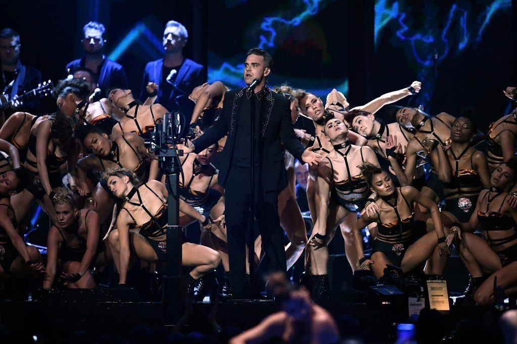 Robbie Williams performs on stage surrounded by women.