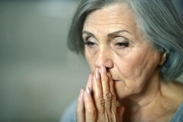 A mature woman looking sad as if she were praying.