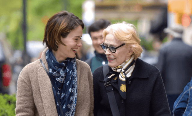 Sarah Paulson and Holland Taylor walk and talk together outside on the street.