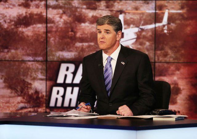 Sean Hannity sits behind a news desk, holding a pen.