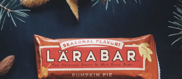 Lara Bar seasonal flavor pumpkin pie on a background with pine trees and nuts.