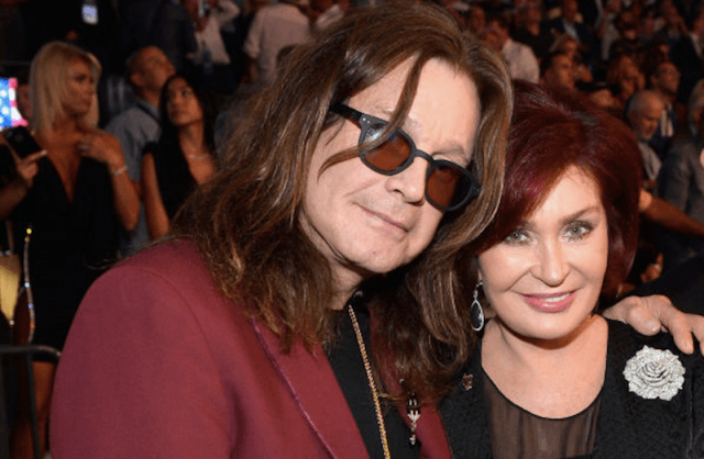 Ozzy poses with his arm around Sharon in a crowded studio.
