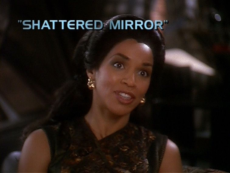 """A woman looks ahead with the words """"Shattered Mirror"""" above her head"""