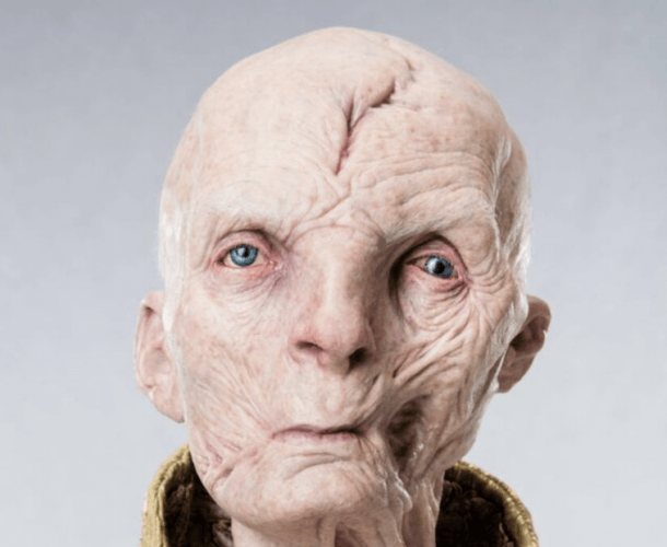 Snoke wearing a gold shirt/robe standing in front of a gray background.