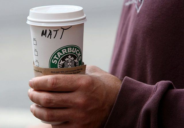 A man holds a Starbucks cup with his name on it.
