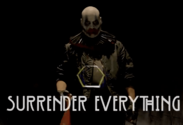 A clown holding a weapon in a dark background.