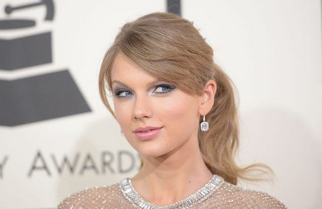 Taylor Swift arrives on red carpet in a silver dress and diamond earrings.