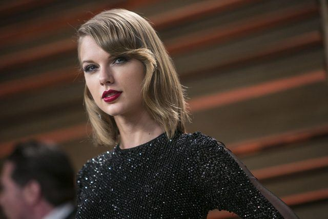 Taylor Swift Arrives at the Oscar party wearing a sequined black gown.