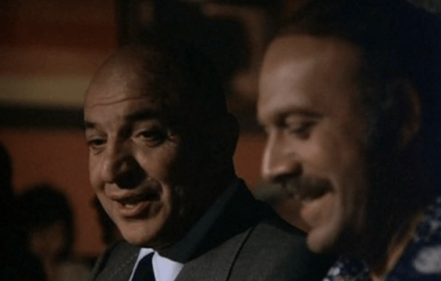 Telly Savalas turning to the side and talking to another person.